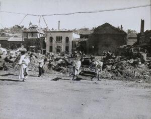 인천상륙작전의 폭격으로 인해 파괴된 건물의 잔해를 지나가는 사람들|1950.9.19. NARA 소장